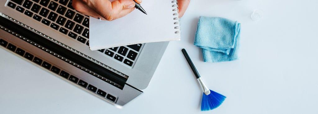 Laptop mit Reinigungsutensilien
