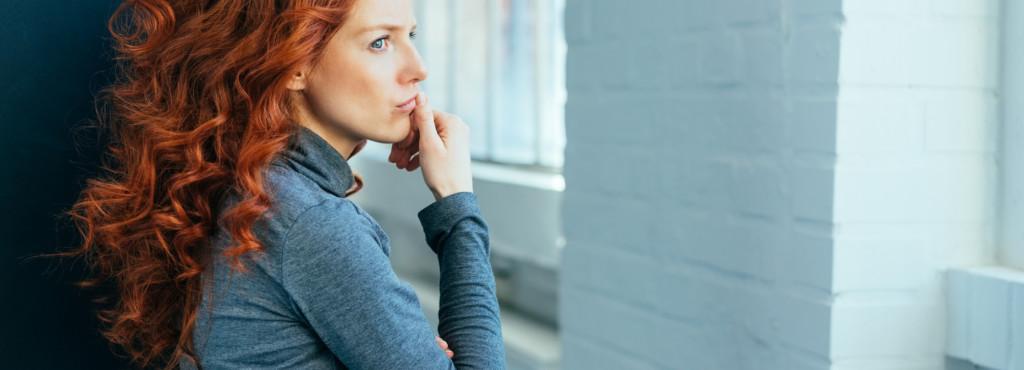 rothaarige Frau verträumt nach draußen schauend