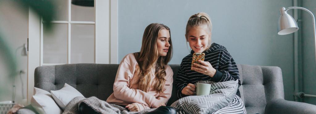 Zwei Mädchen mit Handy auf der Couch