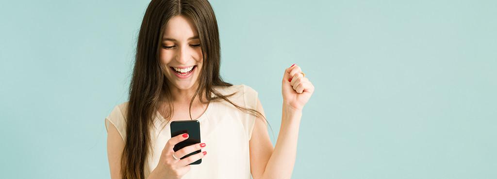 Junge Frau auf das Handy blickend und lachend