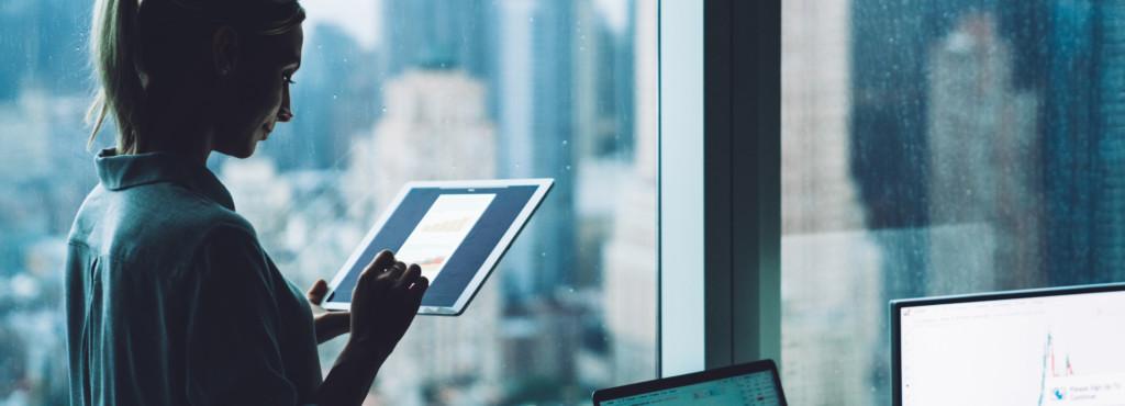 Blonde Frau auf Tablet schauend vor Skyline Kulisse und Charts im Hintergrund auf Bildschirmen