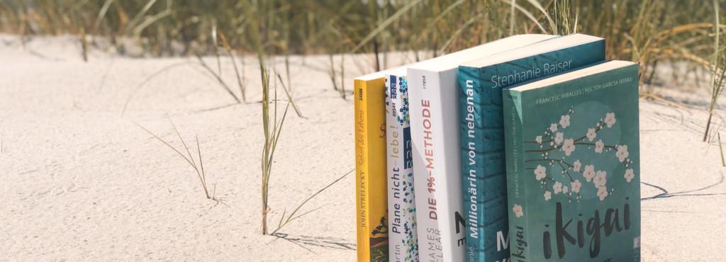 Fünf aufgestellte Bücher im Sand mit Meer im Hintergrund