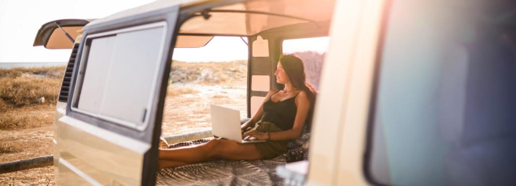 Frau mit Laptop im offenen Van