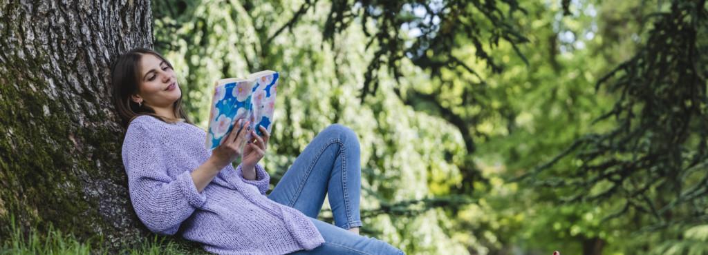 Junge Frau an einen Baum im Schatten lehnend und ein Buch lesend.