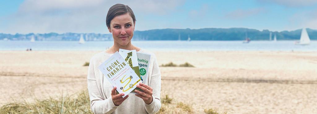 Katinka Tiegs mit drei Büchern in der Hand haltend am Strand, Segelboote auf dem Meer im Hintergrund